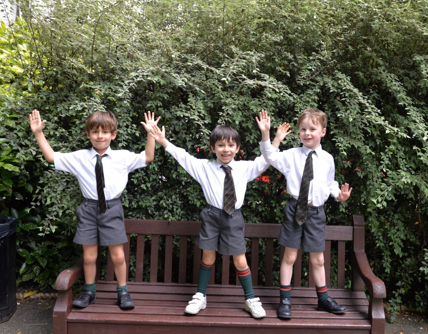 Three UK students standing on a bench at school.